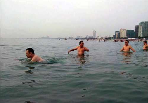 Nguyen Dieu (first from left) and other Da Nangs environment department officials swim at Pham Van Dong beach in the morning of April 30.