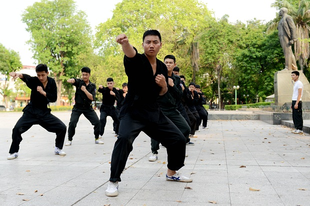 Vietnamese police officer doing martial art workout in Lenine's square.