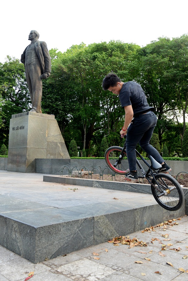 A young boy performing BMX under a statue of Lenine in Lenine's square.