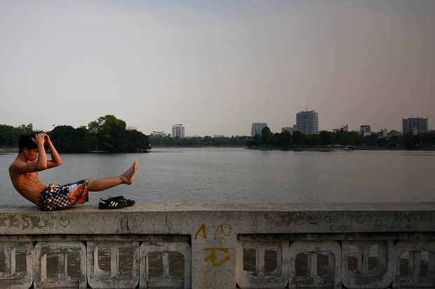 A young men doing some workout in front of the lake of Lenin's Park.