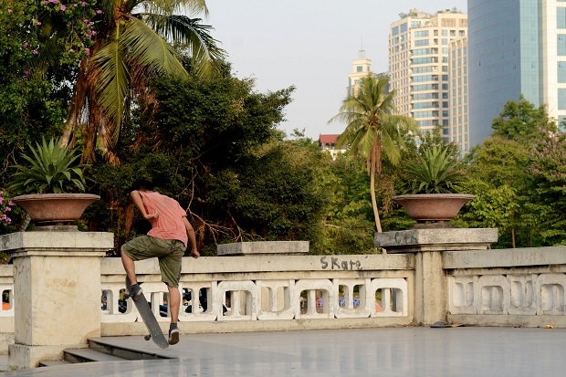 A young boy performing skateboard in Lenine's park.