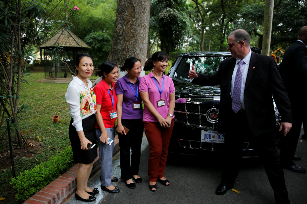 Women pose for a picture next to U.S. President Barack Obama's limousine as a secret service officer asks them to move during Obama's visit at the gardens of the presidential palace in Hanoi, Vietnam May 23, 2016. Photo by Reuters/Carlos Barria