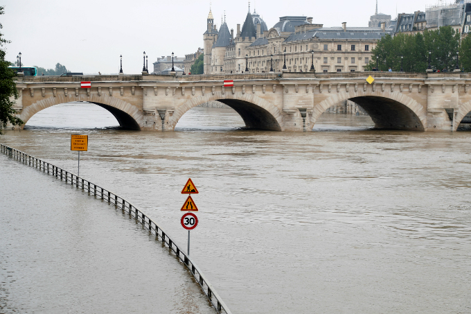 Road signs appear isolated in the rising waters. Photo by Reuters/Charles Platiau