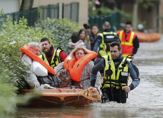 French firefighters on a small boat evacuate residents from a flooded area in Longjumeau, southern Paris. Photo by Reuters/Christian Hartmann