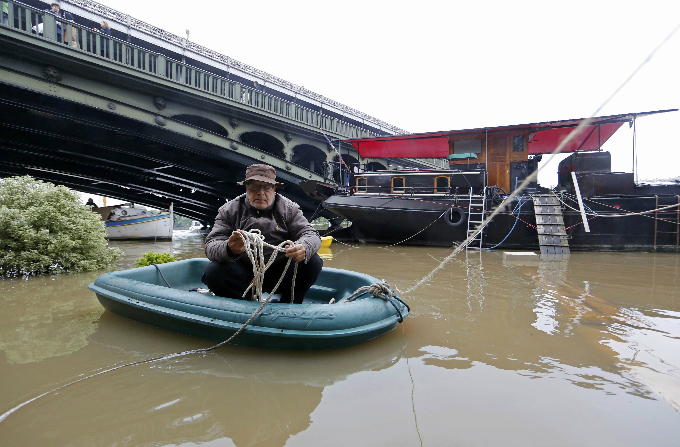 A man sits in a dinghy as he makes his way towards a houseboat along the banks of the Seine River in Paris. Photo by Reuters/Jacky Naegelen