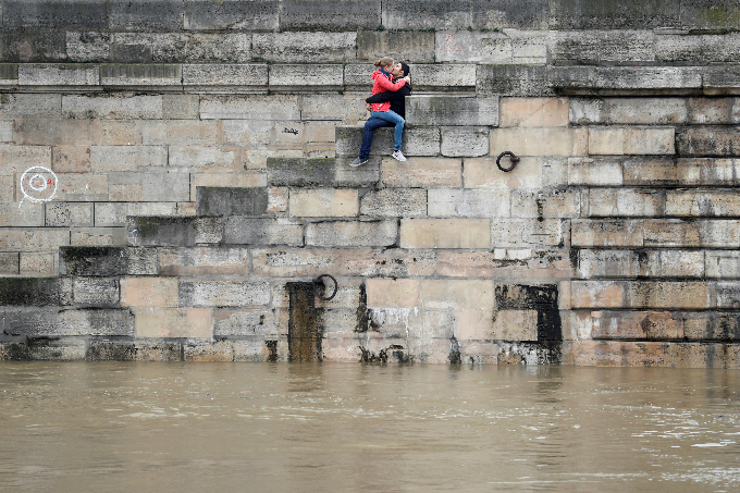 A couple exchanges kisses on the bank of the Seine River. Photo by Reuters/Charles Platiau