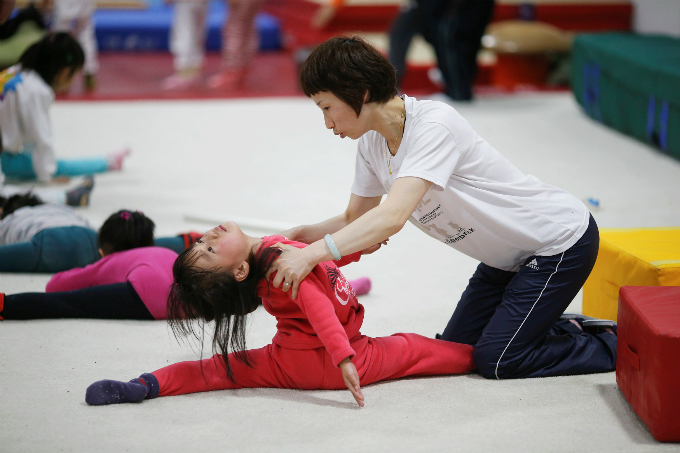 A coach helps a girl during gymnastics lessons. Photo by Aly Song