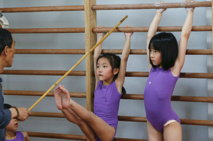 A girl tries to stretch her legs and reach a stick held by her coach during gymnastics lessons