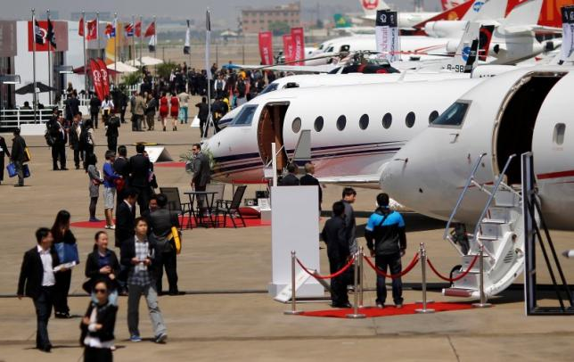 Guests walk next to aircraft during the Asian Business Aviation Conference and Exhibition (ABACE) at Hongqiao International Airport in Shanghai in this April 15, 2014 file photograph. Photo by Reuters/Carlos Barria/Files