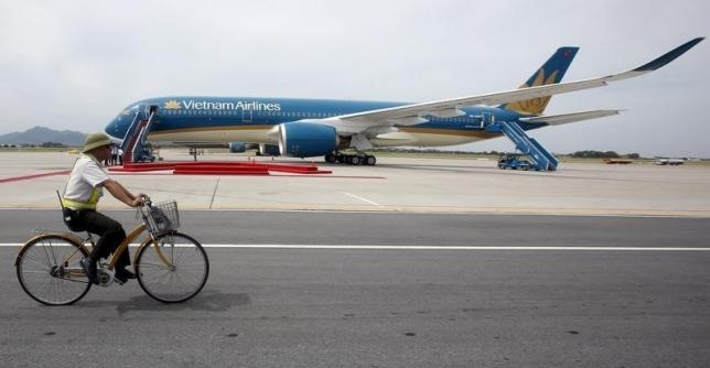 A security guard cycles near an Airbus A350-900 aircraft during its delivery ceremony at Noi Bai International Airport in Hanoi July 2, 2015. Photo by Reuters/Kham
