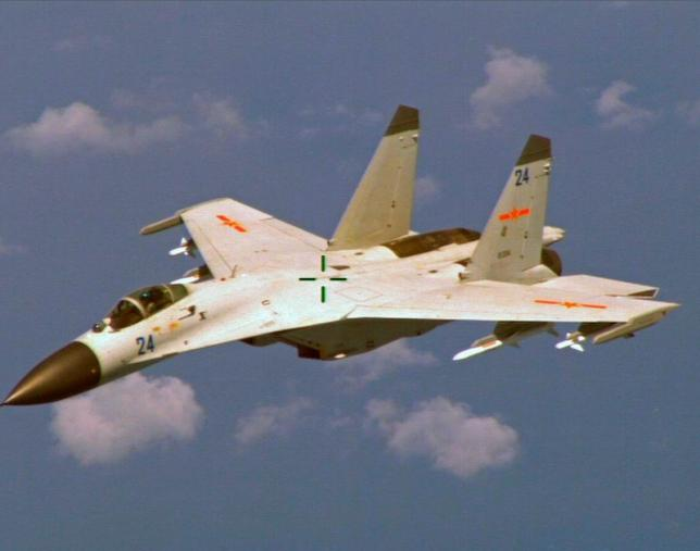 A Chinese J-11 fighter jet is seen flying near a U.S. Navy P-8 Poseidon about 215 km (135 miles) east of Chinas Hainan Island in this U.S. Department of Defense handout photo taken August 19, 2014. Photo by Reuters//U.S. Navy