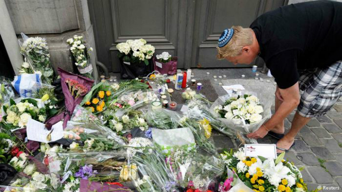 Man inspecting flowers laid before the Jewish Museum following the shooting. Photo by Reuters/Belgian Police