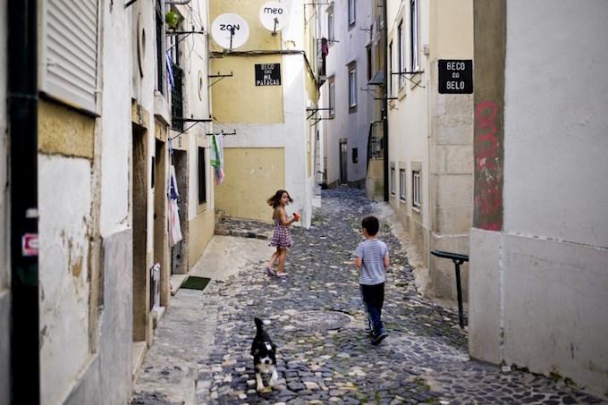 Kids play in the streets of Alfama neighborhood in Lisbon on June 29, 2016.