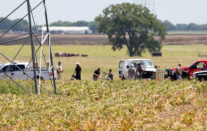 The partial frame of a hot air balloon is visible above a crop field as investigators comb the wreckage of a Saturday morning accident that left 16 people feared dead when the balloon crashed in Maxwell, Texas, U.S. July 30, 2016. Photo by Reuters