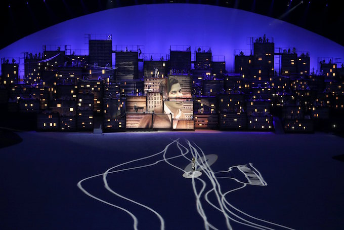 2016 Rio Olympics - Opening ceremony - Maracana - Rio de Janeiro, Brazil - 05/08/2016. Brazilian model Giselle Bundchen walks across the stage as an image of Brazilian composer Tom Jobim is seen projected on constructions meant to represent buildings. Photo by Reuters/Marko Djurica