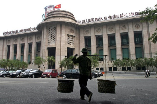 A man walks past the State Bank of Vietnam in Hanoi. Photo by Reuters