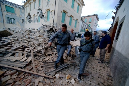 Rescuers carry a man from the rubble after a strong earthquake hit Amatrice on August 24, 2016. Photo by AFP/Filippo Monteforte
