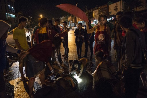 people surrounding a person involved in a road accident at the scene as they wait for Vientiane Rescue volunteers to arrive in Vientiane, Laos. Photo by AFP/Lillian Suwanrumpha