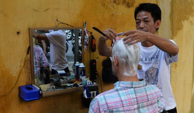 Street barber Nguyen Van Tu. Photo by AFP/Hoang Dinh Nam