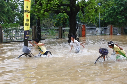 Three students passing a street in the central city of Hue submerged following floods. Photo by VnExpress/Nguyen Dong