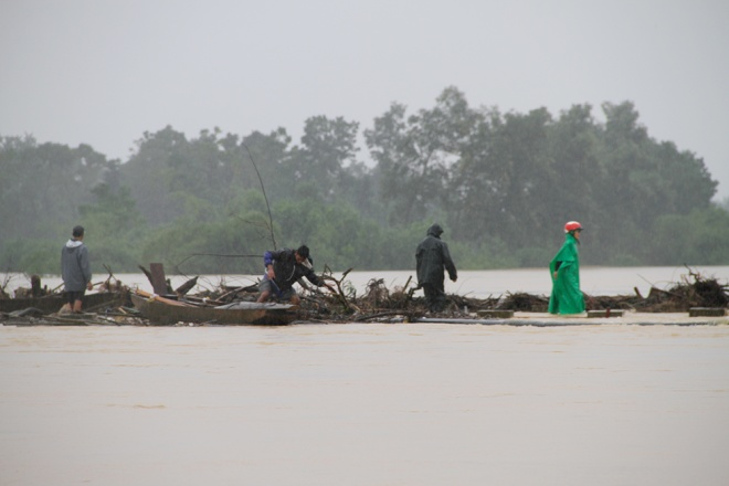 people-risk-life-to-pick-up-logs-among-floods