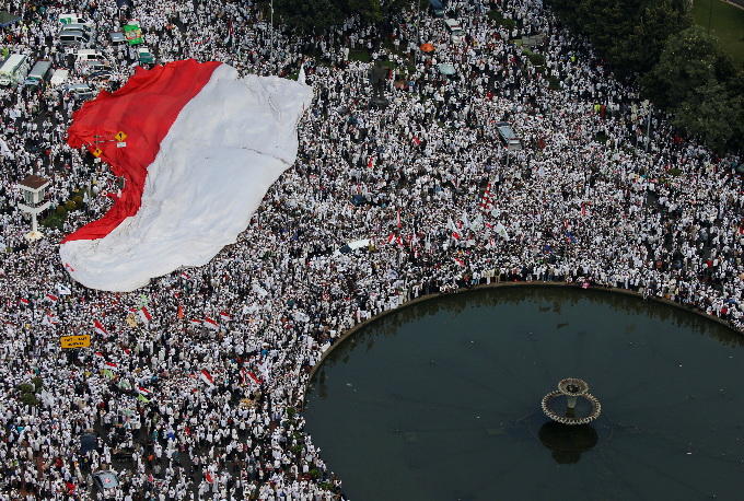 Members of hardline Muslim groups hold a big national flag as they attend a protest against Jakartas incumbent governor Basuki Tjahaja Purnama, an ethnic Chinese Christian running in the upcoming election, in Jakarta, Indonesia, November 4, 2016. Photo by Reuters/Beawiharta