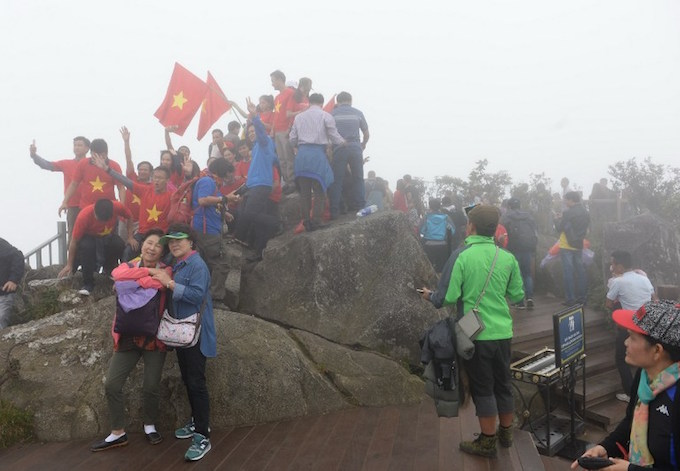 This picture taken on October 1, 2016 shows tourists posing for photos at the very top of Fansipan Mountain in northern Sapa tourist town. Photo by AFP/Hoang Dinh Nam