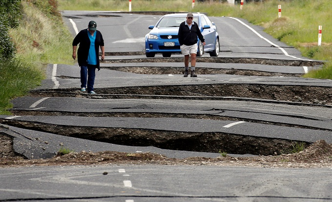 Local residents Chris and Viv Young look at damage caused by an earthquake, along State Highway One near the town of Ward, south of Blenheim on New Zealands South Island, November 14, 2016. Photo by Reuters/Anthony Phelps