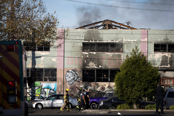 Smoke rises from a smoldering building where a fire broke out during an electronic dance party late Friday evening, resulting in at least nine deaths and many unaccounted for in the Fruitvale district of Oakland, California, U.S. December 3, 2016. Photo by Reuters/Stephen Lam