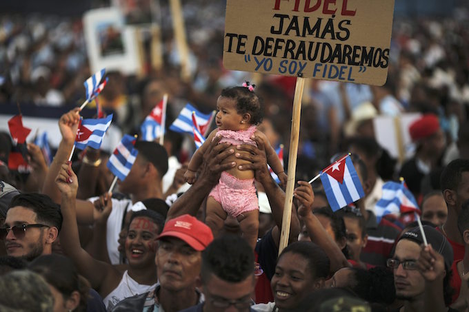 An baby is raised in the air as people wait for the arrival of the caravan carrying the ashes of Cubas late President Fidel Castro in Santiago de Cuba, Cuba, December 3, 2016. Photo by Reuters/Carlos Barria