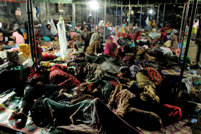 Indonesian women and children displaced by an earthquake rest under a tent in Pidie Jaya, Aceh province, on December 9, 2016. The shallow 6.5-magnitude quake levelled hundreds of homes, mosques and businesses across Aceh province, one of the areas worst affected by the destructive 2004 tsunami. GATHA GINTING / AFP
