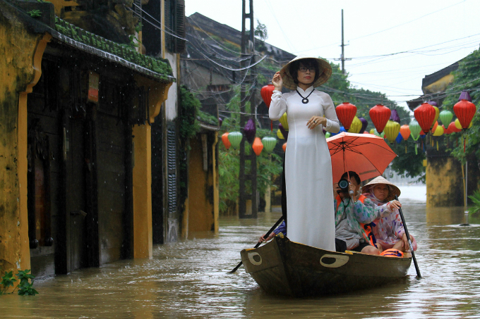 A Vietnamese girl with Ao Dai traditional long dress on a boat on a submerged street in the ancient town