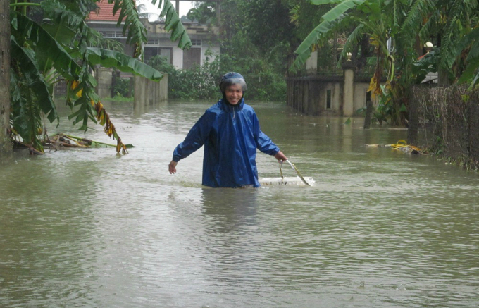 A resident was crossing a submerged road in Huong Tra Town
