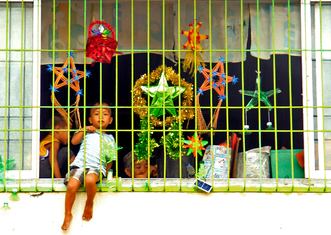 A boy sits at a window as he celebrates Christmas Day at the evacuation center before Typhoon Nock-ten is expected to strike Legazpi City, Albay province, central Philippines December 25, 2016. REUTERS/Stringer
