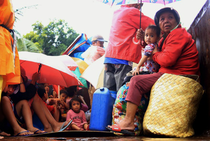 Residents sit in a truck after the local government implemented preemptive evacuations at Barangay Matnog, Daraga, Albay province on December 25, 2016, due to the approaching typhoon Nock-Ten. Photo by AFP