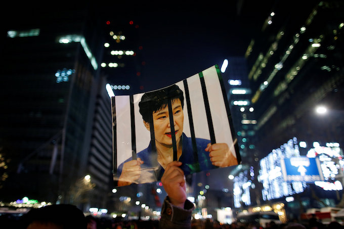 A man holds up a picture bearing an image of South Korean President Park Geun-hye as he attends a ceremony to celebrate the new year after a protest demanding Parks resignation, in Seoul, South Korea, December 31, 2016. Photo by Reuters/Kim Hong-Ji