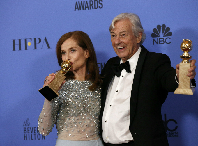 Actress Isabelle Hubbert and producer Paul Verhoeven pose backstage with their awards for Best Actress in a Motion Picture - Drama and Best Motion Picture - Foreign Language for Elle, at the 74th Annual Golden Globe Awards in Beverly Hills, California, U.S., January 8, 2017. REUTERS/Mario Anzuoni