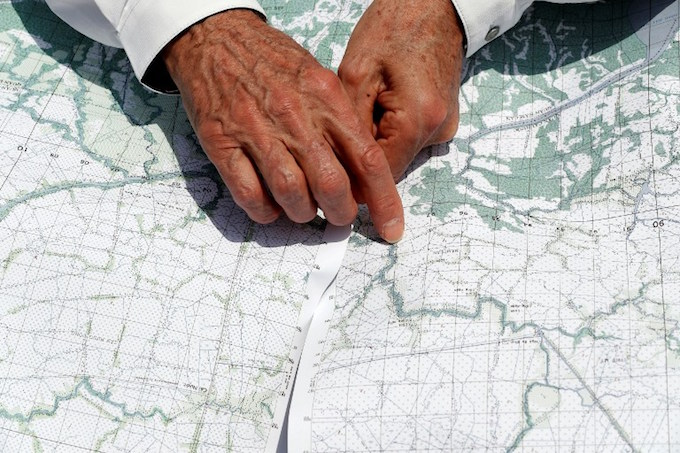 US Secretary of State John Kerry uses a map to identify the location where the action took place for which he received the Silver Star, while on a boat tour in the Mekong River Delta on January 14, 2017. Kerry is in Vietnam, his fourth and final trip to the communist nation where he served during the war. Alex Brandon / POOL / AFP