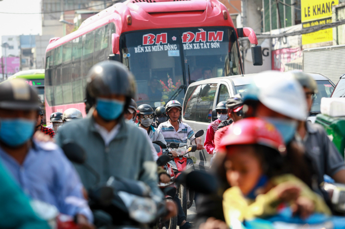 A bus from Ho Chi Minh City to Binh Dinh are surrounded by motorcycles and cant move an inch due to congestion