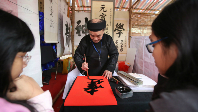 A calligrapher is writing meaningful words for the Festivals attendee. Photo by VnExpress/Ngoc Thanh