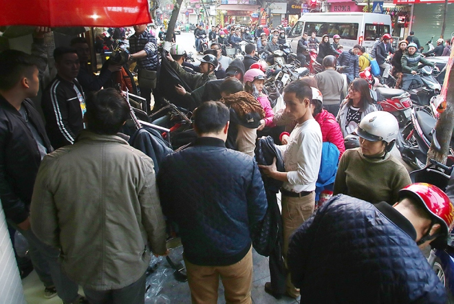 Shoppers occupy part of a street in Hanoi as clothes shops present their special Tet offer on the sidewalk. The frenetic scene is all over downtown streets like Hang Bong, Ba Trieu, Phong Ngoc Thach, Chua Boc, Xuan Thuy and Pho Hue.