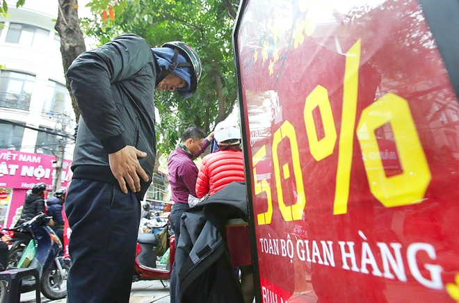 A man tries a new sweater right on the sidewalk, next to a shiny notice of 50 percent discount. Hanoi has been forecast to be a chilly in early morning during the holiday.