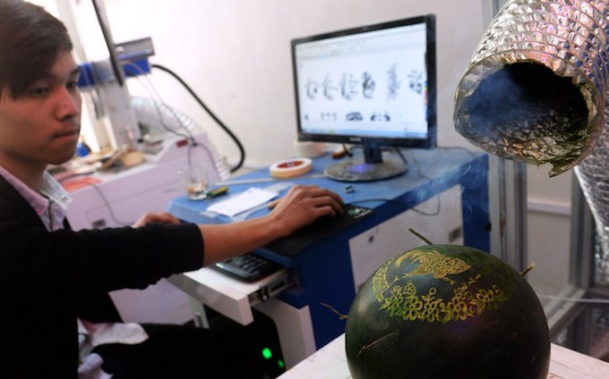 This picture taken on January 24, 2017 shows an technician using a computer to create a laser-carving on a watermelon at Nguyen Van Minhs workshop in Hanoi. Photo by AFP/Hoang Dinh Nam