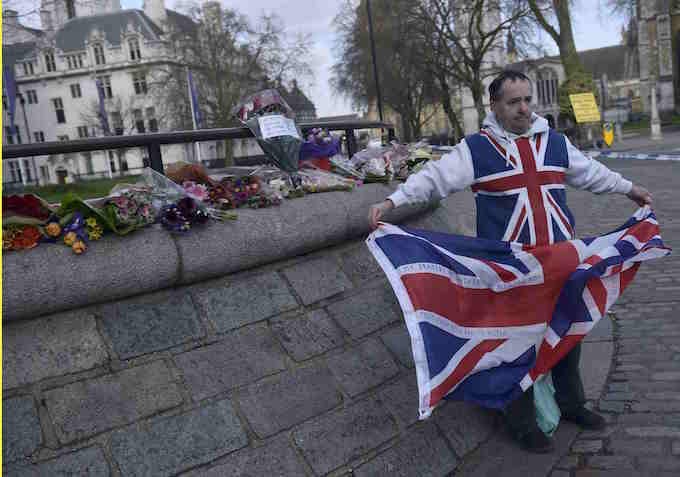 A man holds a Union Flag near the Houses of Parliament in Westminster the day after an attack, in London, Britain March 23, 2017. Photo by Reuters/Hannah McKay