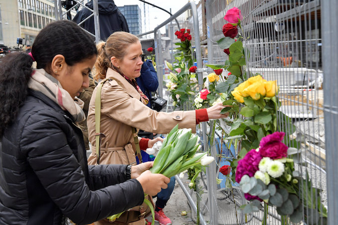 People lay flowers near the crime scene, near the Ahlens department store, in central Stockholm the morning after a hijacked beer truck plowed into pedestrians on Drottninggatan and crashed into Ahlens department store on Friday, killing four people, injuring 15 others. Photo by TT News Agency/Anders Wiklund/via Reuters