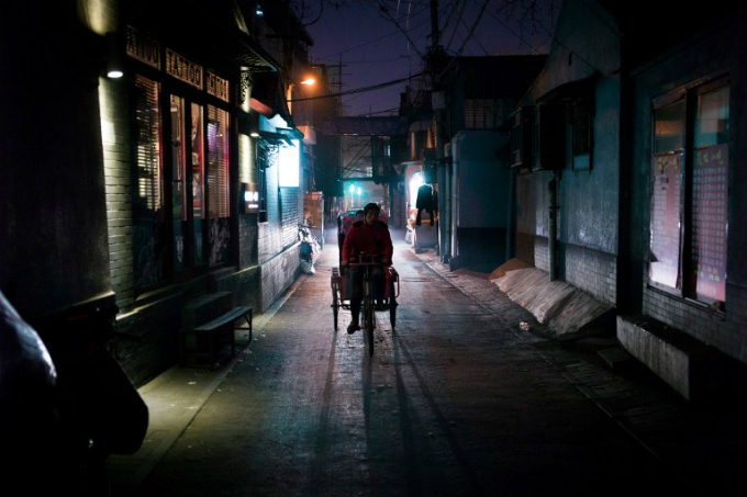a man riding his tricycle in a hutong in Beijing. Photo by AFP/Fred Dufour