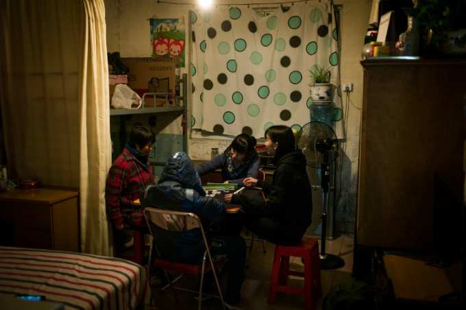 people playing mahjong in their home in a hutong in Beijing. Photo by AFP/Fred Dufour