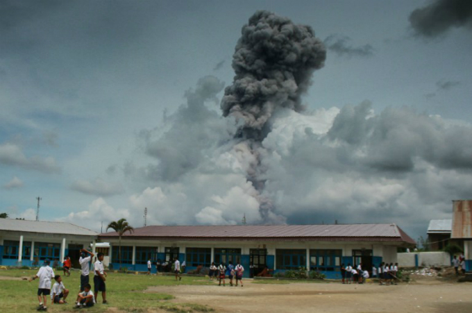 Indonesian pupils playing with the background of Mount Sinabung volcano spewing thick smoke. Photo by AFP/Tibta Pangin