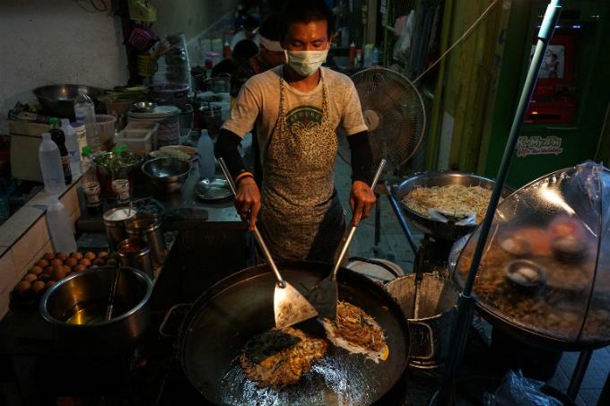 A man making food at a street stall in the Phrakanong district of Bangkok. Photo by AFP/Lillian Suwanrumpha