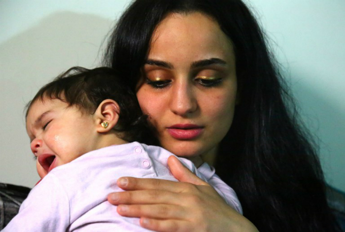 Twenty-three year old Islam Maytat from Morocco comforts her one of her two children, Maria, during an interview in the Kurdish-majority city of Qamishli in northern Syrian
